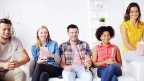 Friends with popcorn and beer watching tv at home. Friendship, leisure, people and entertainment concept - happy friends eating popcorn, drinking beer or cider stock footage