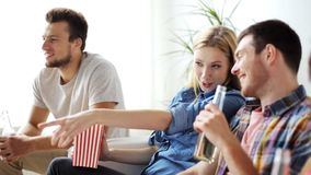 Friends with popcorn and beer watching tv at home. Friendship, leisure, people and entertainment concept - happy friends eating popcorn, drinking beer or cider stock video