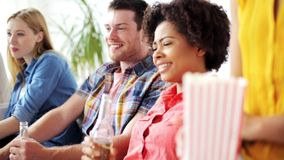 Friends with popcorn and beer watching tv at home. Friendship, leisure, people and entertainment concept - happy friends eating popcorn, drinking beer or cider stock video footage