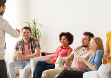 Friends with popcorn and drinks talking at home Royalty Free Stock Image