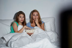 Friends with popcorn and watching tv at home Stock Photos