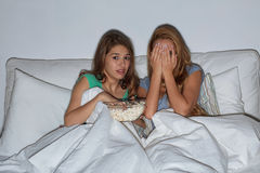 Friends with popcorn and watching tv at home Stock Photo