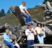 Hiking with Friends. Group of friends sitting on huge pile of drift wood with their small dogs Royalty Free Stock Photos