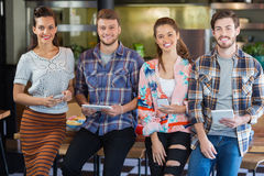 Friends posing with mobile phones and digital tablets in restaurant. Portrait of friends posing with mobile phones and digital tablets in restaurant stock images