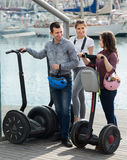 Friends posing near segways on shore Royalty Free Stock Photo