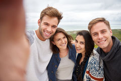 Friends posing for selfie outdoors in nature. Smiling group of friends posing for a selfie while standing together outdoors stock photography