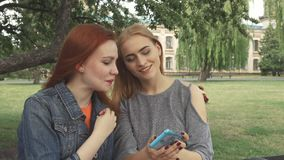 Two girls taking a selfie outdoors. Friends posing and taking selfies. Then discuss the photos. Women have a rest in park near university stock video footage