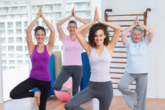 Friends practicing tree pose in fitness studio Royalty Free Stock Photos