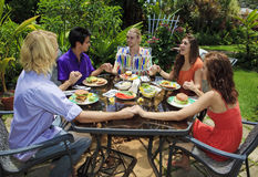 Friends praying together before lunch. Friends at an outdoor bar-b-que holding hands in prayer and meditation prior to enjoying their meal stock photography