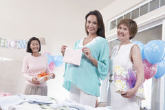 Friends With Pregnant Woman Holding Baby Shower Gift Royalty Free Stock Image