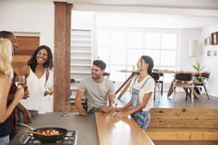 Friends Prepare And Serve Food For Dinner Party At Home Together Royalty Free Stock Photo
