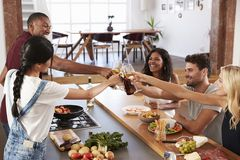 Friends Prepare And Serve Food For Dinner Party At Home Together Stock Images