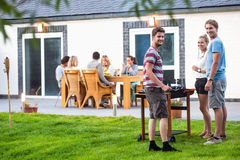 Friends preparing barbecue in back yard Stock Photography