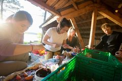 Friends Preparing Food In Shed At Forest. Multiethnic male and female friends preparing food in shed at forest Royalty Free Stock Photos
