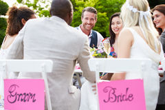 Friends Proposing Champagne Toast At Wedding. Sitting Outside Around Table Royalty Free Stock Photo