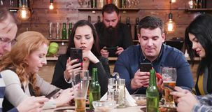 Friends in pub all looking at smartphone instead of talking to each other
