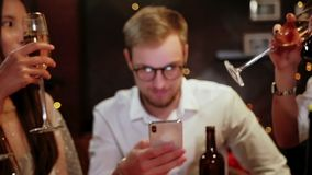 Friends in a pub celebrate and have fun, one guy is looking at a smartphone, and not talking to other people. The