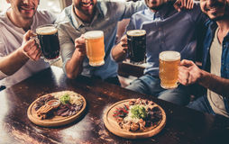 Friends in pub. Cropped image of handsome guys drinking beer and smiling while resting in pub Royalty Free Stock Image