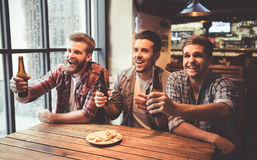 Friends at the pub. Handsome friends are drinking beer, cheering for sport team and smiling while resting at the pub Royalty Free Stock Photos