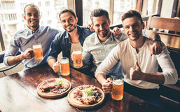 Friends in pub. Handsome friends are drinking beer, looking at camera and smiling while resting in pub Stock Image