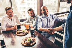 Friends in pub. Handsome friends are drinking beer, meeting friends, talking and smiling while resting in pub Stock Photos