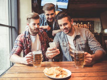 Friends at the pub. Handsome friends are drinking beer, using a smartphone and smiling while resting at the pub Royalty Free Stock Images