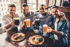 Friends in pub. Handsome guys are drinking beer, looking at camera and smiling while resting in pub Stock Photo