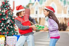 Friends Pulling Christmas Gift Royalty Free Stock Photos