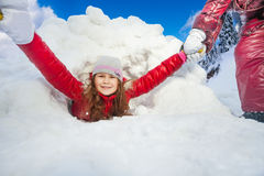 Friends are pulling smiling girl from snow tunnel Royalty Free Stock Photography