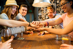 Friends putting hands on top of each other at bar Royalty Free Stock Photos