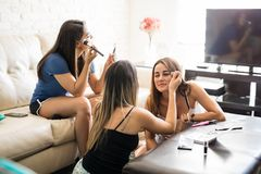 Friends putting on makeup at home. Group of three female friends putting some makeup on and getting ready to go out Stock Photo