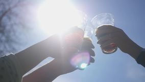 Friends raise glasses on a festive day with various drinks against the blue sky and the bright summer sun. Party in