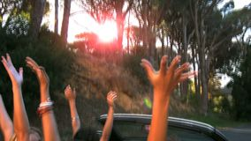 Friends raising their hands in the air while man is driving stock video