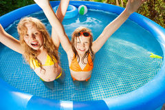 Friends raising their hands up in swimming pool Royalty Free Stock Images