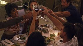 Friends raising a toast at party. Diverse group of friends sitting at dinner table and toasting wineglasses at party. Young people enjoying drinks at dinner out stock video