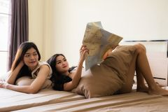 Friends read global map for vacation plan. Portrait of beautiful lesbian couple or roommate happy women on bed look at map to set vacation travel plan to foreign Stock Photography
