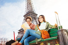 Friends reading map of Paris sitting on the bench Royalty Free Stock Photography