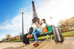 Friends reading map sitting near the Eiffel Tower Royalty Free Stock Image