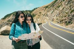 Friends reading map while standing on road. Two good friends reading map together while standing on the road with a background of stunning mountains stock image