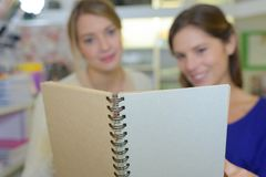 Friends reading shopping list in notebook. Notebook Stock Photography