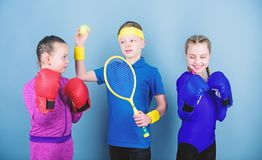Friends ready for sport training. Sporty siblings. Child might excel completely different sport. Girls kids with boxing. Sport equipment and boy tennis player royalty free stock image