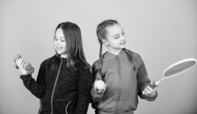 Friends ready for training. Ways to help kids find sport they enjoy. Girls cute kids with sport equipment dumbbells and. Tennis racket. We love sport. Child royalty free stock photography