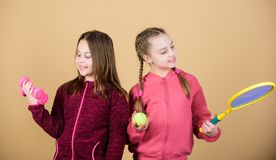 Friends ready for training. Ways to help kids find sport they enjoy. Girls cute kids with sport equipment dumbbells and. Tennis racket. We love sport. Child stock images