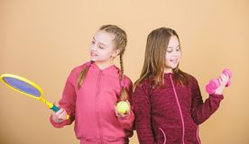 Friends ready for training. Ways to help kids find sport they enjoy. Girls cute kids with sport equipment dumbbells and. Tennis racket. We love sport. Child royalty free stock images
