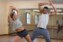 Friends rehearsing dance against mirror at studio Stock Photography