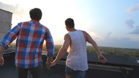 Friends rejoices life during standing on roof at sunset time. Gay couple raising hands showing joyful emotions. Men