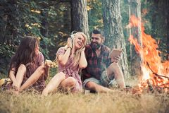 Friends relax at bonfire flame with sparks in vintage style. People camping at fire in forest. Women and bearded man at royalty free stock photo