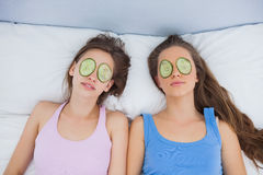 Friends relaxing in bed with cucumber on eyes Stock Photo