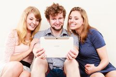 Friends relaxing browsing internet on tablet. Friends browsing surfing internet on tablet. Young people men guy and women girls sitting on sofa relaxing at home Stock Image