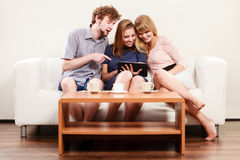 Friends relaxing browsing internet on tablet. Royalty Free Stock Photography